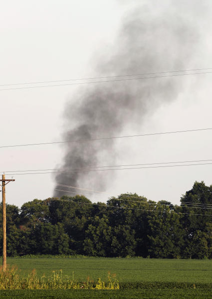 FILE - In this July 10, 2017, file photo, smoke rises in the air after a military transport plane crashed into a field near Itta Bena, Miss., on the western edge of Leflore County, as seen from U.S. Highway 82. Investigators say bad maintenance practices at a Georgia air force base missed a deteriorating propeller blade that broke off six years later as a U.S. Marine Corps transport plane cruised over Mississippi at 20,000 feet, causing the KC-130T to break into pieces and plunge into a soybean field, killing 15 Marines and a Navy corpsman, according to the report on the causes of the July 10, 2017, crash, released Wednesday, Dec. 5, 2018. (AP Photo/Andy Lo, File)