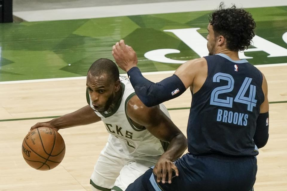 Milwaukee Bucks' Khris Middleton drives past Memphis Grizzlies' Dillon Brooks during the first half of an NBA basketball game Saturday, April 17, 2021, in Milwaukee. (AP Photo/Morry Gash)