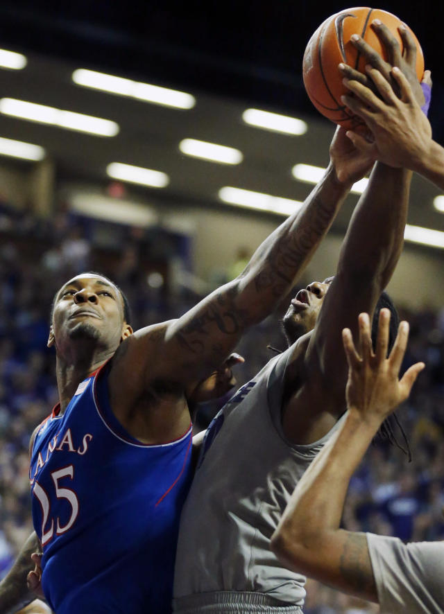 Kansas forward Tarik Black (25) battles for a rebound against Kansas State forward D.J. Johnson (50) during the first half of an NCAA college basketball game in Manhattan, Kan., Monday, Feb. 10, 2014. (AP Photo/Orlin Wagner)