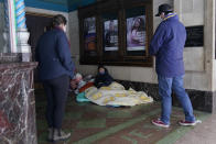 A woman who identified herself as Caroline and using blankets to keep warm outside the Majestic Theater, is encouraged by Morgan Handley, left, and Pastor Gavin Rogers, right, to seek shelter, Tuesday, Feb. 16, 2021, in San Antonio. (AP Photo/Eric Gay)