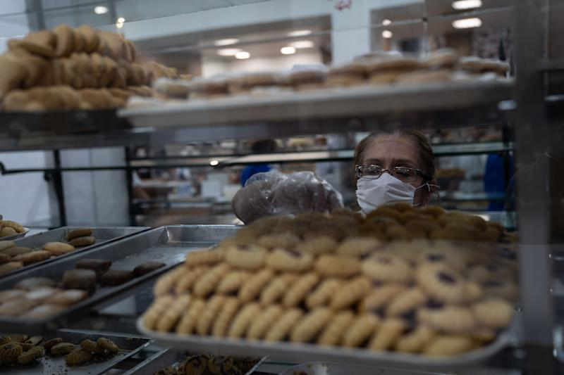 MEXICO CITY, MEXICO - MARCH 24: A bakery employee wearing a protective mask selects products during phase two of contingency measures to avoid the spread of COVID-19 on March 24, 2020 in Mexico City, Mexico. Beginning Monday, Mexico City ordered the closure of museums, bars, gyms, churches, theaters, with the exception of restaurants, in an attempt to contain COVID-19 pandemic. (Photo by Toya Sarno Jordan/Getty Images)