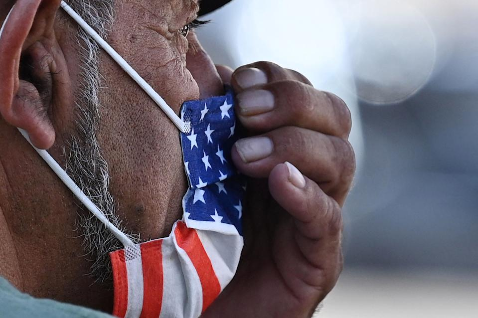 A man adjusts his American flag face mask on July 19, 2021 on a street in Hollywood, California, on the second day of the return of the indoor mask mandate in Los Angeles County due to a spike in coronavirus cases. - The US surgeon general on July 18 defended a renewed mask mandate in Los Angeles, saying other areas may have to follow and adding that he is