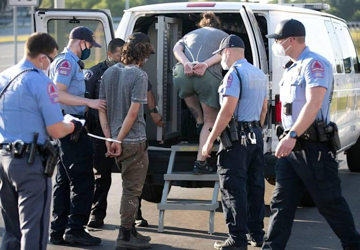 Raleigh police officers load the last of the nearly 18 protesters that were arrested for blocking traffic on Capital Blvd. near the Peace Street bridge on Thursday, July 2, 2020 in Raleigh, N.C.