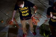"""Activists wearing """"COUNT EVERY VOTE"""" t-shirts coil electrical cord after a street dance party across the street from where votes are being counted in Philadelphia"""