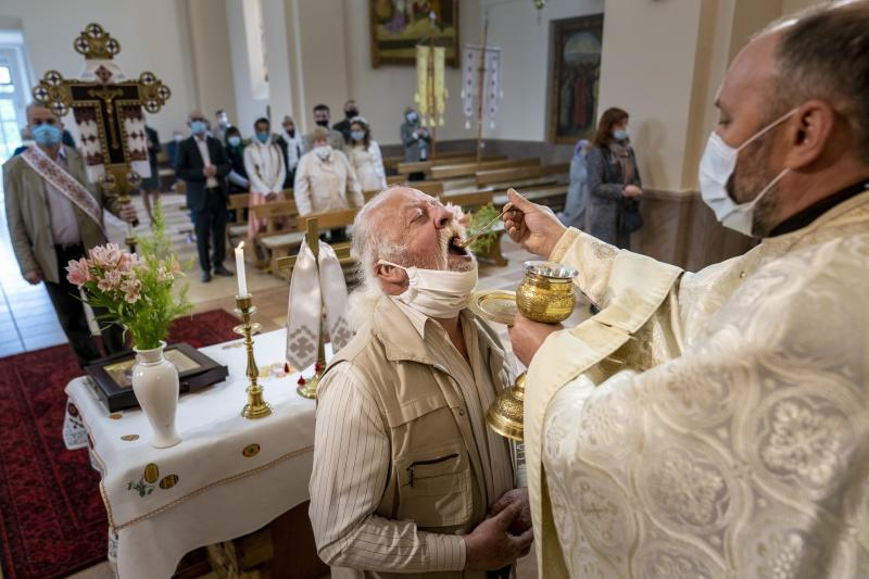 In this photo taken on Sunday, May 24, 2020,  Ukrainian Greek Catholic Church priest, Father Vasyl Gasynets distributes Holy Communion during Sunday Mass at a church in Chernivtsi, Ukraine. Gasynets has returned to conducting services at his Greek Catholic church in priestly raiment, but wearing a mask while distributing communion. (AP Photo/Evgeniy Maloletka)