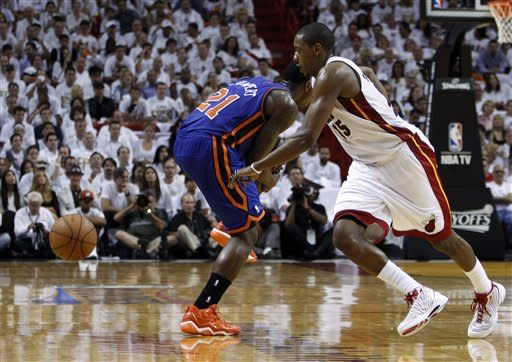New York Knicks' Iman Shumpert (21) pulls on his leg after injuring it in the second half during an NBA basketball game in the first round of the Eastern Conference playoffs in Miami, Saturday, April 28, 2012. At right is Miami Heat's Mario Chalmers. (AP Photo/Lynne Sladky)