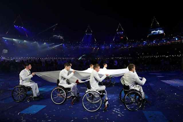 LONDON, ENGLAND - AUGUST 29: The Paralympic flag is carried by members of the Great Britain U22 Wheelchair basketball team during the Opening Ceremony of the London 2012 Paralympics at the Olympic Stadium on August 29, 2012 in London, England. (Photo by Dan Kitwood/Getty Images)