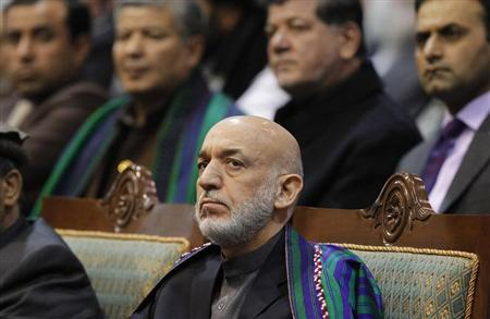 Karzai attends during the last day of the Loya Jirga, in Kabul