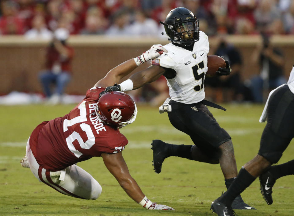 Army running back Kell Walker (5) avoids a tackle by Oklahoma defensive end Amani Bledsoe (72) in the first half of an NCAA college football game in Norman, Okla., Saturday, Sept. 22, 2018. (AP Photo/Sue Ogrocki)
