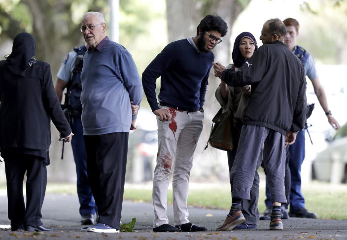 <p>People stand across the road from a mosque in central Christchurch, New Zealand. (AP Photo/Mark Baker) </p>