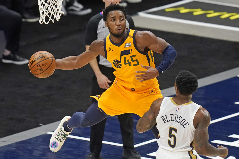 Utah Jazz guard Donovan Mitchell (45) passes the ball as New Orleans Pelicans guard Eric Bledsoe (5) watches during the first half of an NBA basketball game Tuesday, Jan. 19, 2021, in Salt Lake City. (AP Photo/Rick Bowmer)