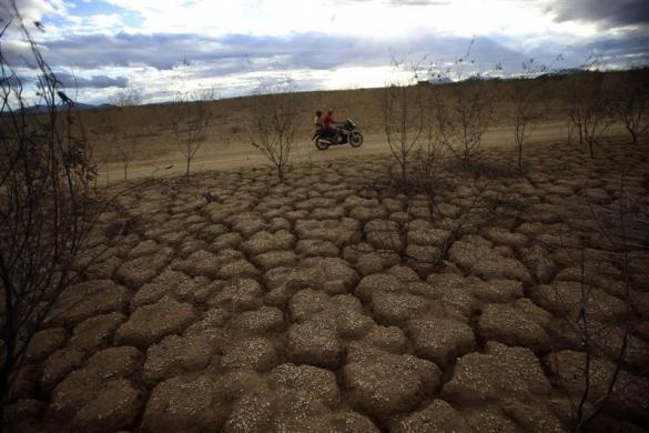 Residents ride a motorcycle over the dried Rio de Contas river in Porto Alegre community in Bahia state, northeast Brazil May 3, 2012.