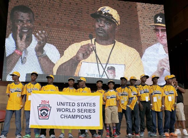 Members of the Jackie Robinson West All Stars Little League baseball team participate in a rally and listen to manager Darold Butler on the big screen as they celebrate the team's U.S. Little League Championship Wednesday, Aug. 27, 2014, in Chicago. (AP Photo/Charles Rex Arbogast)