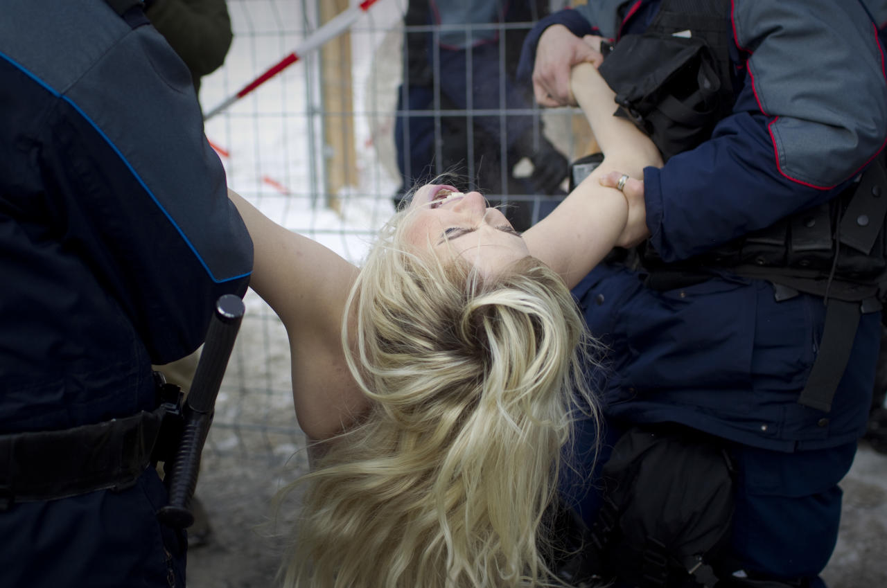 A topless Ukrainian protester is arrested by Swiss police after climbing up a fence at the entrance to the congress center where the World Economic Forum takes place in Davos, Switzerland Saturday, Jan. 28, 2012. The activists are from the group Femen, which has have become popular in Ukraine for staging small, half-naked protests against a range of issues including oppression of political opposition. (AP Photo/Anja Niedringhaus)