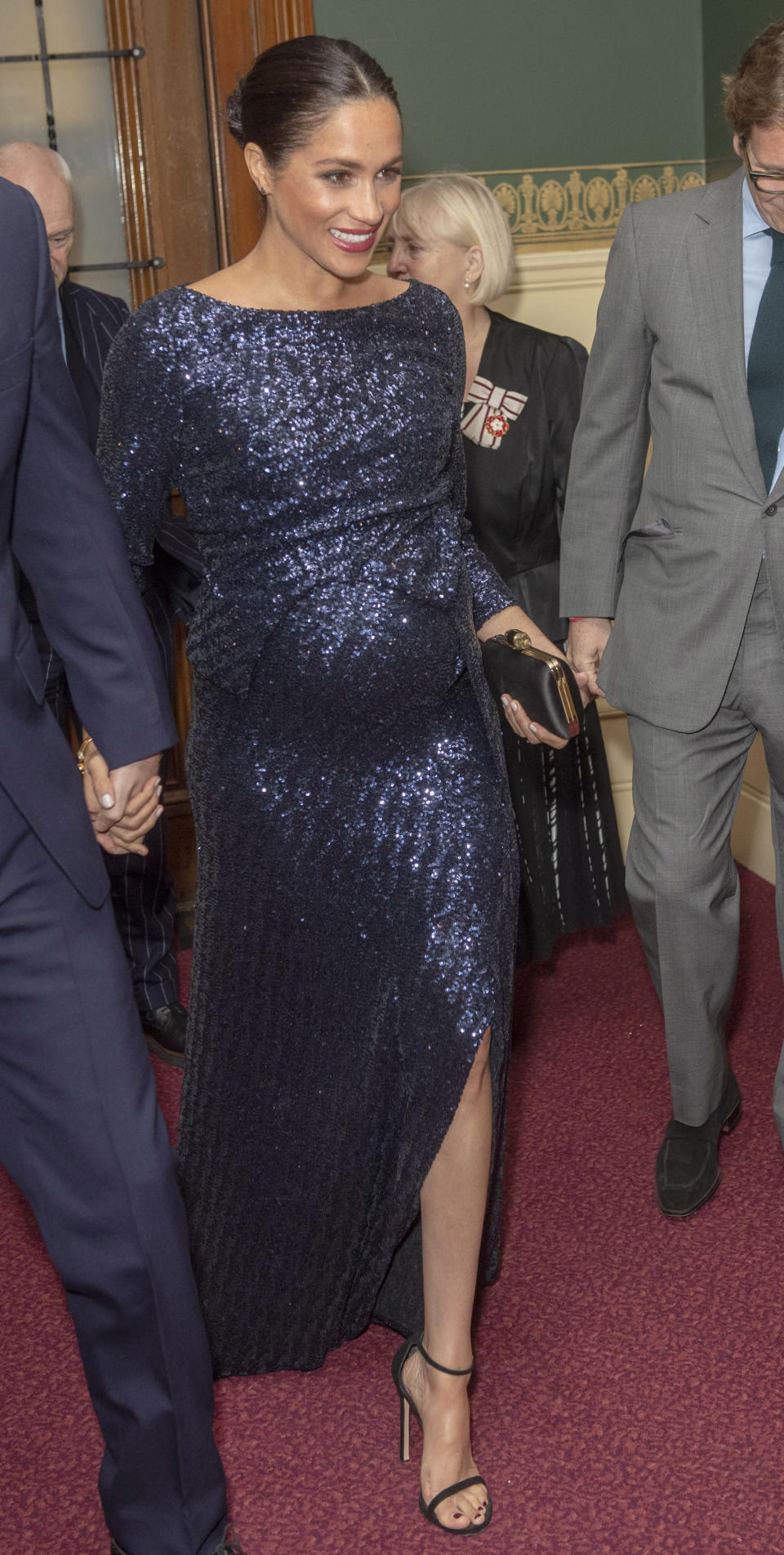 <p>After a quick outfit change, the Duchess of Sussex dazzled at the premiere of the Cirque du Soleil's 'Totem' at the Royal Albert Hall. For the evening, the mother-to-be dressed her bump in a £3,475 midnight blue Roland Mouret gown finished with Stuart Weitzman's £450 black 'Nudist' sandals. Her go-to Givenchy satin clutch bag and Princess Diana's Heirloom bracelet completed the ensemble. <em>[Photo: Getty]</em> </p>