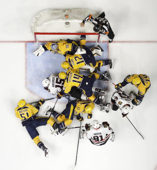 Nashville Predators and Chicago Blackhawks pile in front of the net after Predators goalie Pekka Rinne (35), of Finland, blocked a shot during the second period in Game 4 of a first-round NHL hockey playoff series Thursday, April 20, 2017, in Nashville, Tenn. (AP Photo/Mark Humphrey)