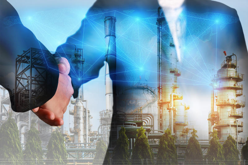 Two people shaking hands with an energy facility in the background
