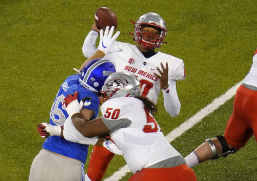 New Mexico quarterback Trae Hall, top, passes the ball as Air Force defensive end Michael Purcell, front left, tangles with New Mexico offensive lineman Teton Saltes in the first half of an NCAA college football game Friday, Nov. 20, 2020, at Air Force Academy, Colo. (AP Photo/David Zalubowski)