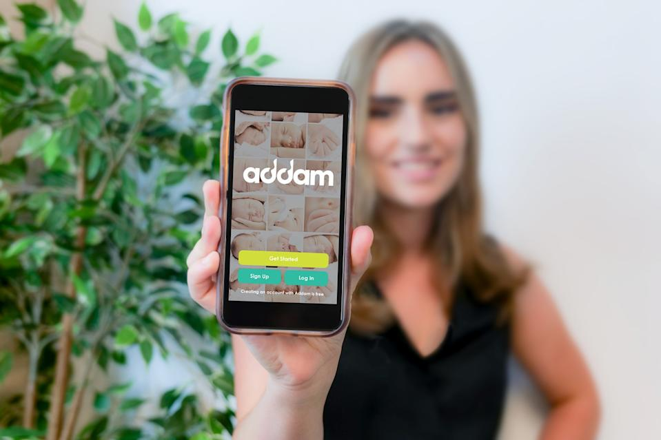 A woman holding a phone displaying the Addam app, a sperm donor matching app created by City Fertility