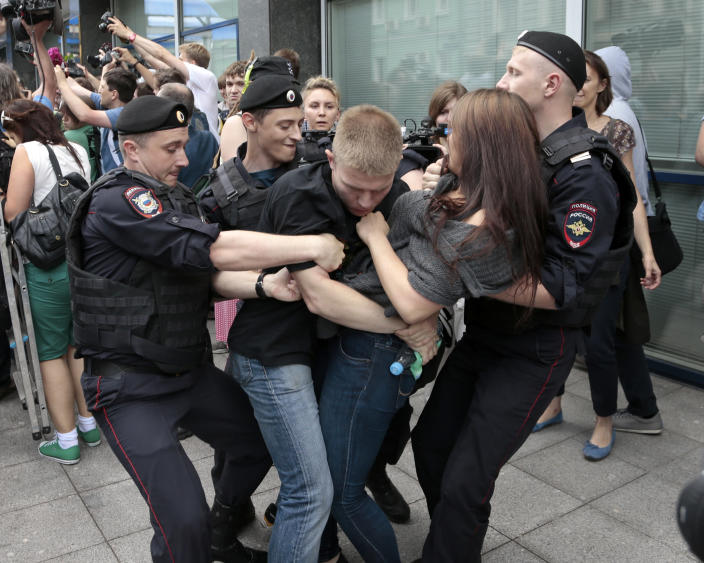 """Police officers detain gay rights activists as they gathered near the State Duma, Russia's lower parliament chamber, in Moscow, Russia, Tuesday, June 11, 2013. Protesters attempted to rally outside the Russian State Duma before what is expected to be a final vote on the bill banning """"propaganda of nontraditional sexual relations."""" More than two dozen activists were detained in Moscow on Tuesday as they were protesting a bill that stigmatizes the gay community and bans the giving of information about homosexuality to children. (AP Photo/Ivan Sekretarev)"""