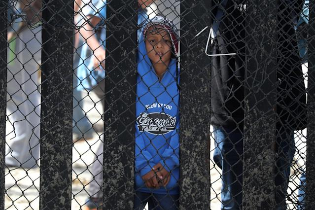 <p>A boy who is with a group of members of a migrant caravan from Central America and their supporters look through the U.S.-Mexico border wall at Border Field State Park before making an asylum request, in San Diego, California, April 29, 2018. (Photo: Lucy Nicholson/Reuters) </p>