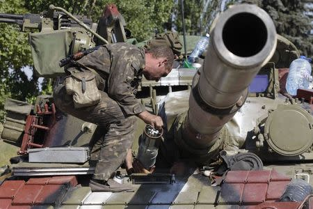 A Ukrainian serviceman loads a shell onto a tank at a checkpoint in the southern coastal town of Mariupol, September 5, 2014. REUTERS/Vasily Fedosenko