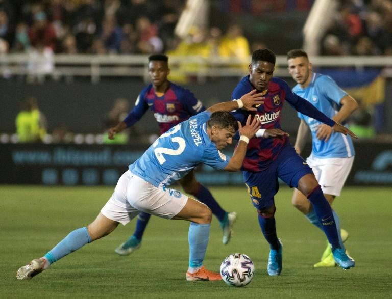 Close contact: Barcelona defender Junior Firpo (right) tussles with Ibiza defender Kike Lopez