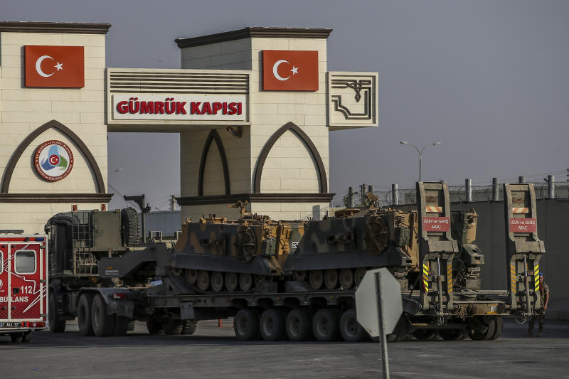 A Turkish forces truck transporting armoured personnel carriers, crosses the border with Syria in Karkamis, Gaziantep province, southeastern Turkey, Tuesday, Oct. 15, 2019.  Turkey defied growing condemnation from its NATO allies to press ahead with its invasion of northern Syria on Tuesday, shelling suspected Kurdish positions near the border amid reports that Syrian Kurds had retaken a key town. (AP Photo/Emrah Gurel)