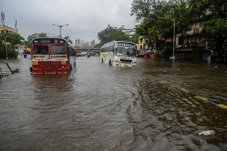 Stranded buses are seen on a flooded road during a heavy monsoon rain in Mumbai on August 4, 2020. (Photo by INDRANIL MUKHERJEE/AFP via Getty Images)