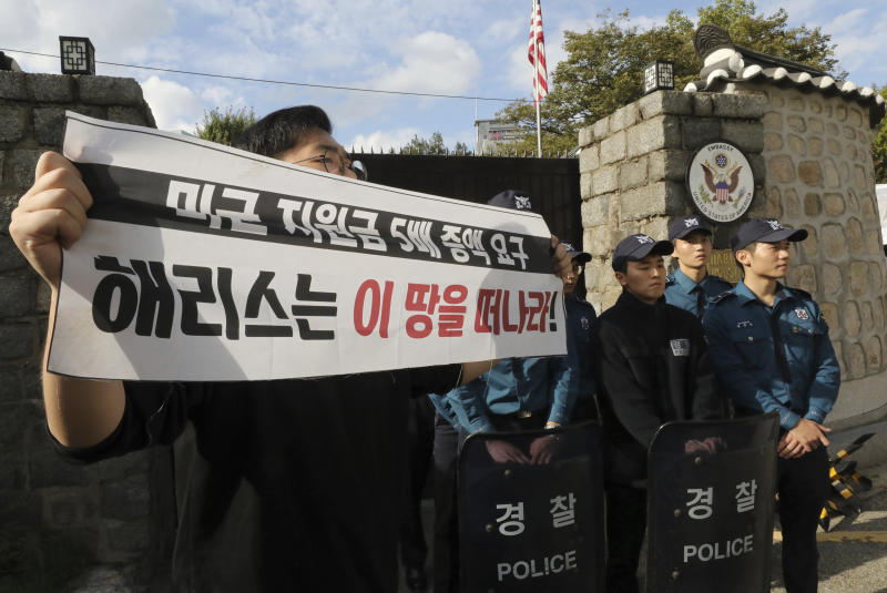 """In this Friday, Oct. 18, 2019, photo, a college student holds a banner in front of the U.S. ambassador's residence in Seoul, South Korea. South Korean police said Saturday, Oct. 19, they beefed up security at the U.S. ambassador's residence in Seoul after a group of anti-American students used ladders to break into the compound. The sign reads """" """"Harris, leave this land!"""" (Chun Jin-hwan/Newsis via AP)"""