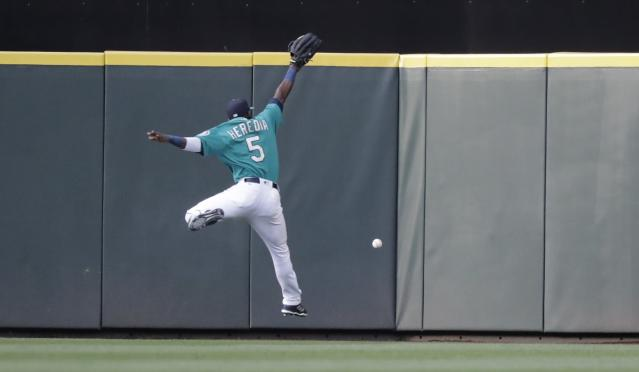 Seattle Mariners left fielder Guillermo Heredia leaps but can't make a catch against the Chicago White Sox during a baseball game, Friday, July 20, 2018, in Seattle. (AP Photo/Ted S. Warren)