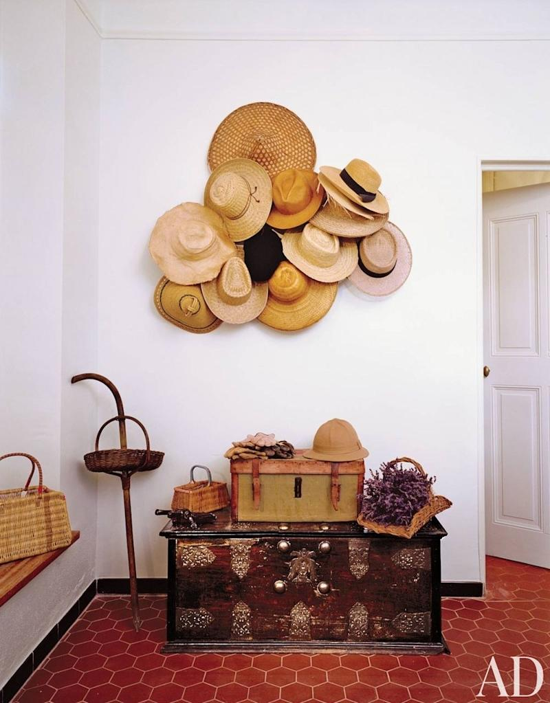 The boot room in a Provence home is decorated with an assortment of hats. Atop the Indian chest is a vintage car box used for picnicking on the property; the walking stick has a basket for collecting truffles.