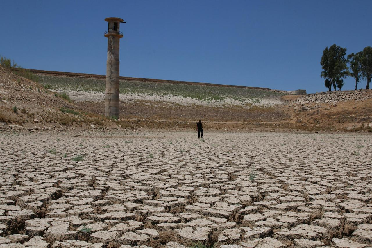 A man walks on the dried cracked bed of the Deraa dam in Deraa Governorate, Syria July 23, 2016. REUTERS/Alaa Al-Faqir