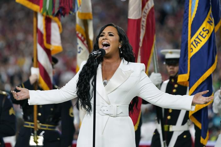 """FILE - Demi Lovato performs the national anthem before the NFL Super Bowl 54 football game between the San Francisco 49ers and the Kansas City Chiefs in Miami Gardens, Fla., on Feb. 2, 2020. Lovato reveals publicly for the first time details about her near-fatal drug overdose in 2018 in """"Demi Lovato: Dancing With the Devil,"""" a four-part docuseries debuting March 23, 2021, on YouTube Originals. (AP Photo/David J. Phillip, File)"""