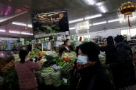 People shop for vegetables at a market in Beijing