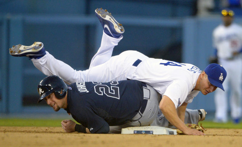 Los Angeles Dodgers second baseman Mark Ellis, top, falls over Atlanta Braves' Chris Johnson after Johnson was forced at second during the third inning in Game 3 of the National League division baseball series Sunday, Oct. 6, 2013, in Los Angeles. (AP Photo/Mark J. Terrill)