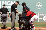Home plate umpire Manny Gonzalez, second from front right, is helped to one knee by Boston Red Sox catcher Christian Vazquez, right, after collapsing during the first inning of a baseball game against the Tampa Bay Rays, Monday, Sept. 6, 2021, at Fenway Park in Boston. Gonzalez Left the game. (AP Photo/Winslow Townson)