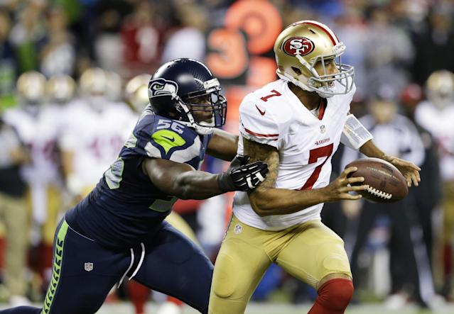 Seattle Seahawks' Cliff Avril, left, forces a fumble by San Francisco 49ers quarterback Colin Kaepernick in the first half of an NFL football game, Sunday, Sept. 15, 2013, in Seattle. The Seahawks recovered the ball on the play. (AP Photo/Elaine Thompson)