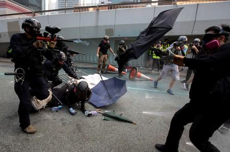 A riot police officer fires pepper-spray projectile toward anti-government protesters demonstrating near the Legislative Council building in Hong Kong