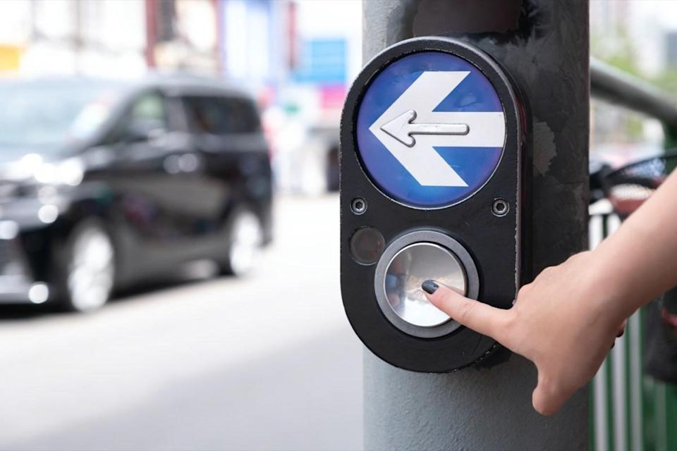 Close up pedestrian crossing call button. Hand pushing button to cross