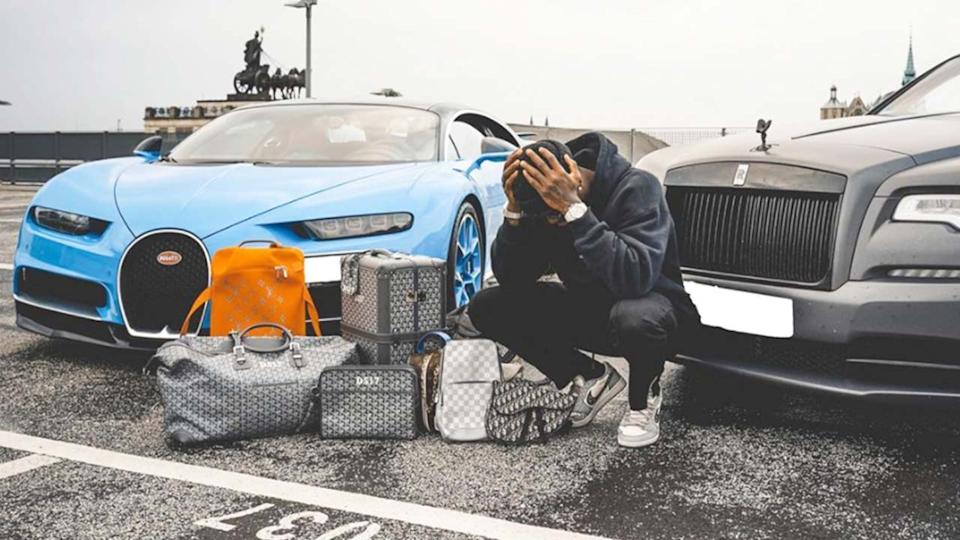 Dennis Schroder (pictured) posing for a photo in front of his cars.