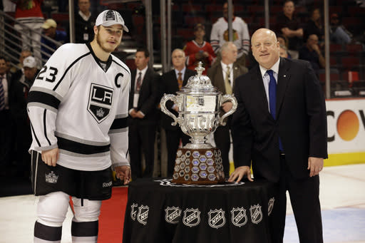 Los Angeles Kings right wing Dustin Brown (23) poses with NFL deputy commissioner Bill Daly with the Clarence S. Campbell Bowl after Los Angeles Kings defeated Chicago Blackhawks 5-4 in the overtime period in Game 7 of the Western Conference finals in the NHL hockey Stanley Cup playoffs Sunday, June 1, 2014, in Chicago. (AP Photo/Nam Y. Huh)