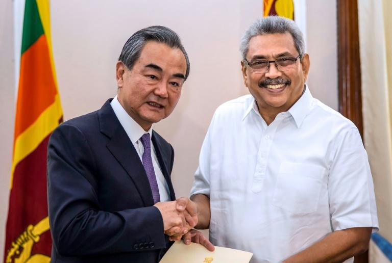 Sri Lankan President Gotabaya Rajapaksa shakes hands with Chinese Foreign Minister Wang Yi during a meeting in Colombo