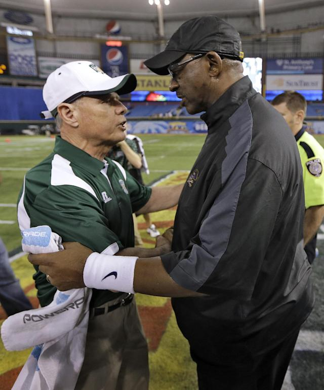 East Carolina head coach Ruffin McNeill, right, shakes hands with Ohio head coach Frank Solich after the Beef 'O' Brady's Bowl NCAA college football game Monday, Dec. 23, 2013, in St. Petersburg, Fla. East Carolina won 37-20. (AP Photo/Chris O'Meara)
