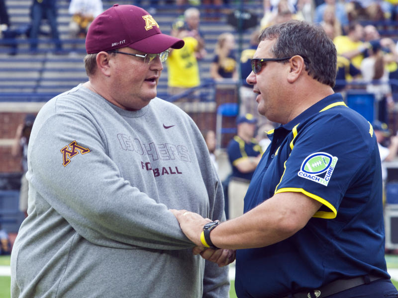Minnesota defensive coordinator and acting head coach Tracy Claeys, left, shakes hands with Michigan head coach Brady Hoke before an NCAA college football game, Saturday, Oct. 5, 2013, in Ann Arbor, Mich. Minnesota coach Jerry Kill has suffered another seizure and did not make the trip. (AP Photo/Tony Ding)