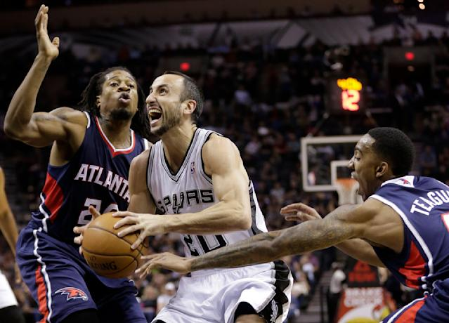 San Antonio Spurs' Manu Ginobili, center, of Argentina, is pressured by Atlanta Hawks' Cartier Martin, left, and Jeff Teague, right, as he drives to the basket during the first half of an NBA basketball game, Monday, Dec. 2, 2013, in San Antonio. (AP Photo/Eric Gay)