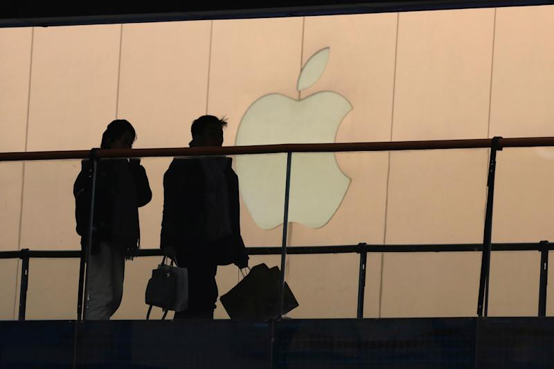 FILE - In this Jan. 3, 2019, file photo, shoppers pass by the Apple store logo at a shopping mall in Beijing. Apple Inc. reports financial results Tuesday, April 30. (AP Photo/Ng Han Guan, File)