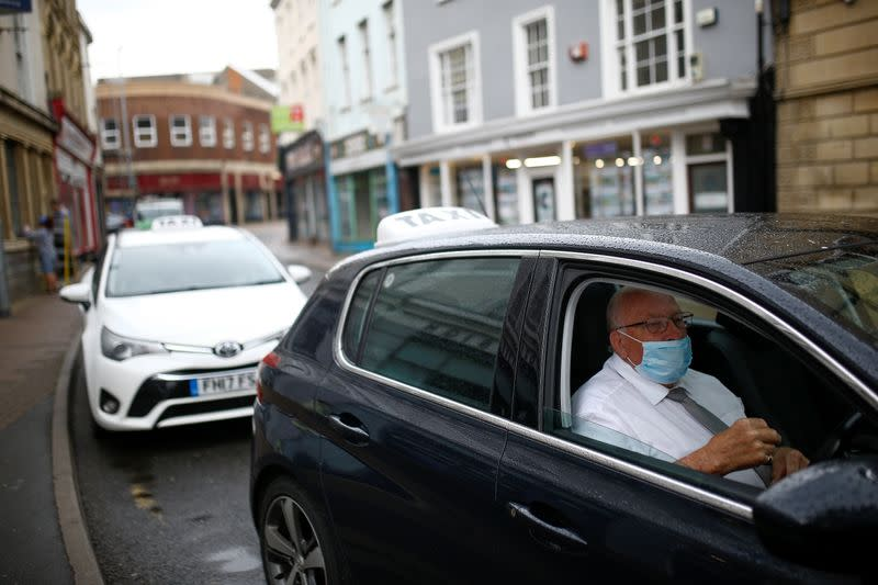 A taxi driver wearing a protective face mask sits at his car in Barnstaple
