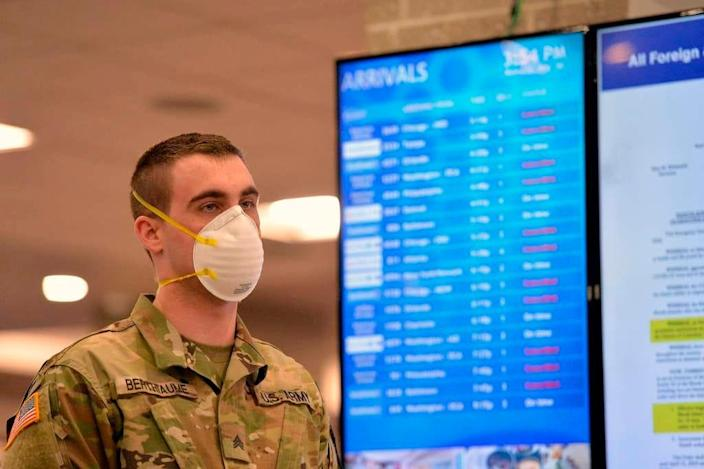 An Army National Guard soldier waits to inform those arriving at an airport in Warwick, Rhode Island, on March 30, 2020, of an order for all travelers to self-quarantine for 14 days.