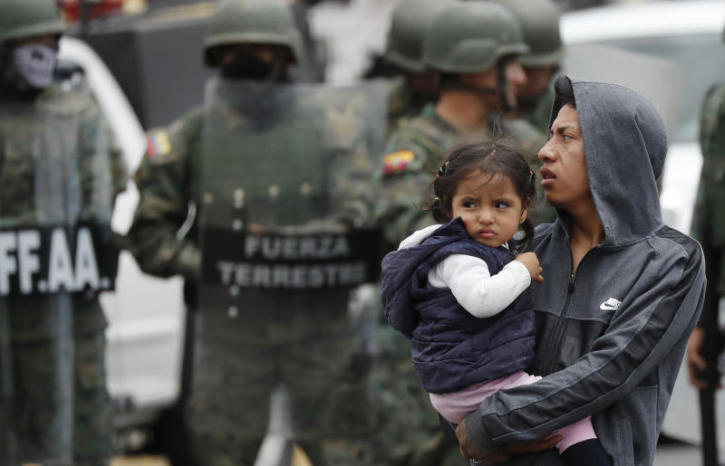 A man carrying a girl leaves a roadblock after soldiers arrive to reopen the road, in Quito, Ecuador, Monday, Oct. 7, 2019. President Lenin Moreno, who earlier declared a state of emergency over a transportation strike, vowed Friday that he wouldn't back down on the decision to end costly fuel subsidies, which doubled the price of diesel overnight and sharply raised gasoline prices. (AP Photo/Dolores Ochoa)